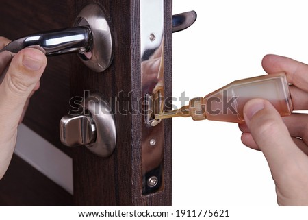 adjusting inner door lock using lubricating oil. indoors. fixing door squealed domestic problem. Foto stock ©