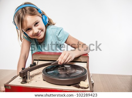 Adjusting the needle while listening to music little girl in blue clothes headphones blonde enjoying vintage sound