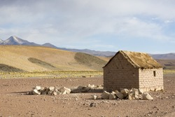 Adobe house in Cerrillos village on Bolivian Altiplano near Eduardo Avaroa Andean Fauna National Reserve with cloudy blue sky, Bolivia