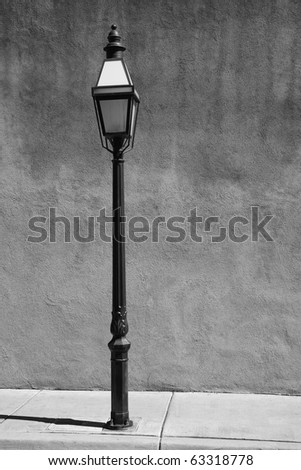 Adobe Wall and Streetlight - An old fashioned street lamp against an adobe style wall. Black and white.