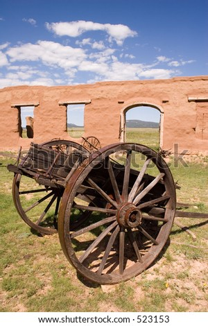 Adobe walls and window gaps form part of the stables and mechanics\' work area, with antique wagon, at old Fort Union National Monument north of Santa Fe, New Mexico