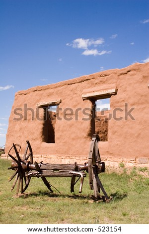 Adobe walls and window gaps form part of the stables and mechanics' work area, with antique wagon, at old Fort Union National Monument north of Santa Fe, New Mexico