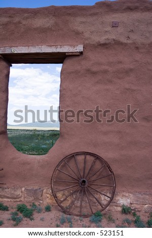 Adobe walls and window gaps form part of the stables and mechanics\' work area, with wagon wheel, at old Fort Union National Monument north of Santa Fe, New Mexico