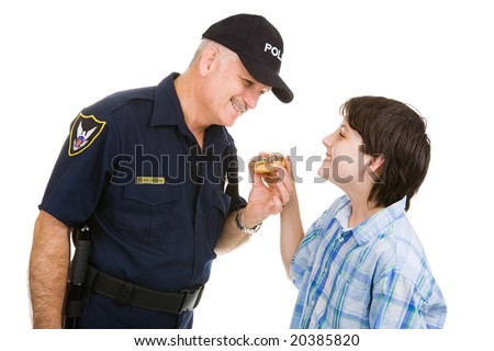 Adolescent boy giving a donut to a friendly police officer.  Isolated on white.