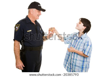 Adolescent boy giving a donut to a police officer.  Isolated on white.