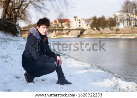 Adolescent boy relaxes by the river in winter, gathers thoughts before going to college after Christmas break. The guy is dressed in warm clothes, he has a pensive face