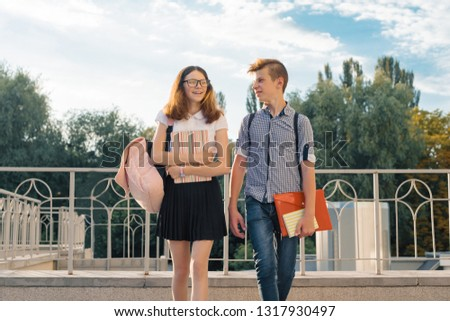 Adolescents students with backpacks, textbooks, go to school. Outdoor portrait of teenage boy and girl 14, 15 years old.