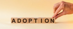 ADOPTION word on block concept. The hand puts a wooden cube with the letter N from the word ADOPTION. The word is written on wooden cubes standing on the yellow surface of the table.