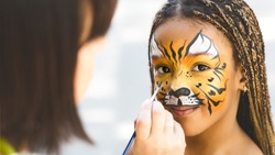 Adorable african-american girl getting tiger face painting in park, empty space