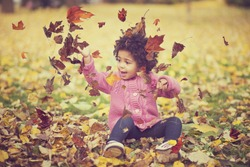 Adorable african american mixed race kid wearing casual clothes playing in park with bunch of leaves, enjoying warm autumn day