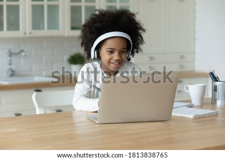 Adorable african ethnicity small girl wearing headphones, looking at computer screen. Happy cute mixed race child enjoying online educational lecture or learning using laptop software application.