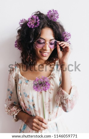 Adorable african girl with curly hairstyle holding allium. Studio shot of black lady in sunglasses posing with purple flowers. #1146059771