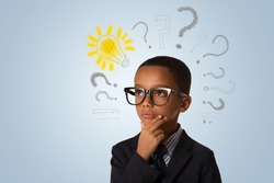 Adorable african little boy wearing glasses and thinking with many question marks and lightbulb. Concept of ideas