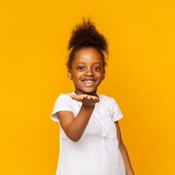 Adorable african little girl sending air kiss to camera, orange studio background