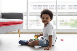 Adorable Afro little boy, boy looking at the camera, cute African American little boy playing with toy cars on the ground at home. kid, playing, holiday concept