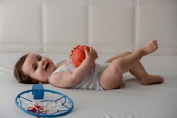 Adorable and happy baby boy playing with basketball on the bed.