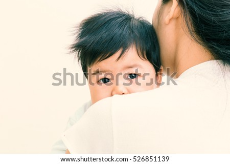 Adorable asian baby sick and unhappy on mom shoulder. (Vintage tone)