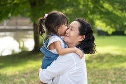 Adorable asian granddaughter is playing and kissing together with grandmother with fully happiness moment in the green park, concept of love and relation of difference generation in family lifestyle