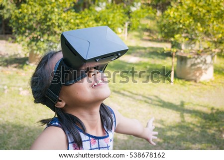 Adorable asian kid with virtual reality playing in a nature outdoors. #538678162