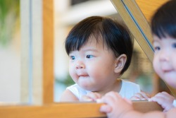 Adorable asian little girl is looking herself in the mirror. The reflection from the mirror with baby girl. she is playing and talking something with herself. happiness moment. kids and home concept