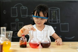 Adorable asian little girl is make easy scientific experimental at home, concept of learn from home, child STEM education and science for kid.