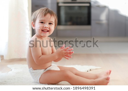 Adorable baby boy applying lotion cream on face and body after shower. Mixed race Asian-German infant wearing diaper clap his hand and laughing at home. Happy child bathing and protect skin.