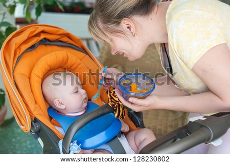 Adorable baby boy first time eating meal with carrots