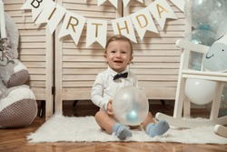 Adorable baby boy holding balloon isolated. Baby 1st birthday.