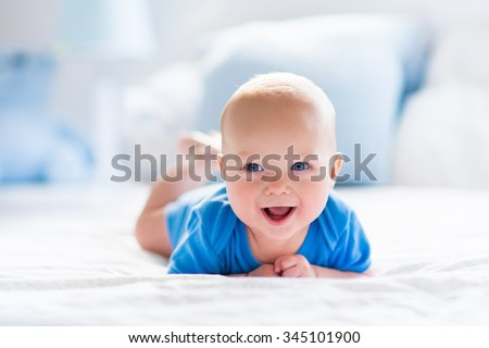 Adorable baby boy in white sunny bedroom. Newborn child relaxing in bed. Nursery for young children. Textile and bedding for kids. Family morning at home. New born kid during tummy time with toy bear.