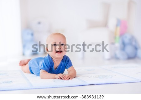 Adorable baby boy in white sunny bedroom. Newborn child relaxing on a rug. Nursery for young children. Furniture, textile and bedding for kids. New born kid during tummy time with toys at a window.