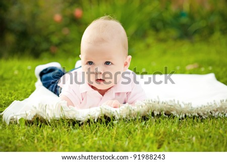 Adorable baby boy laying on grass in spring flowery garden. Shallow depth of fields