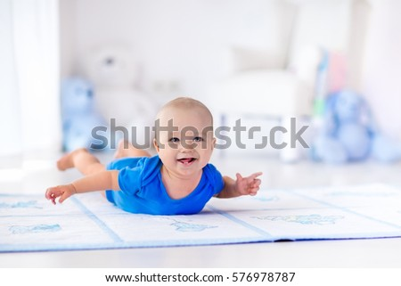 Adorable baby boy learning to crawl and playing with colorful toy in white sunny bedroom. Cute laughing child crawling on a play mat. Nursery interior, clothing and toys for little kids