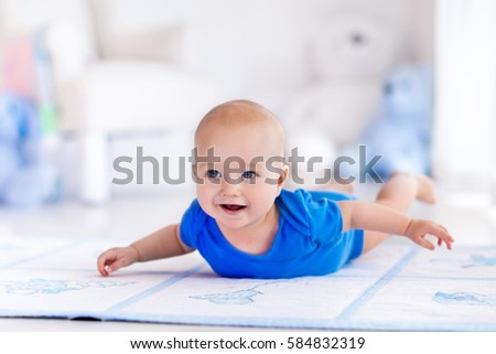 Adorable baby boy learning to crawl and playing with colorful toy in white sunny bedroom. Cute laughing child crawling on a play mat. Nursery interior, clothing and toys for little kids.