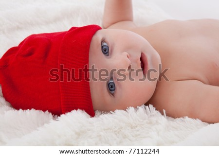 Adorable baby boy lying on soft fur blanket and cushion, smiling with red hat on