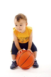 Adorable baby  boy playing with a basketball isolated over a white background