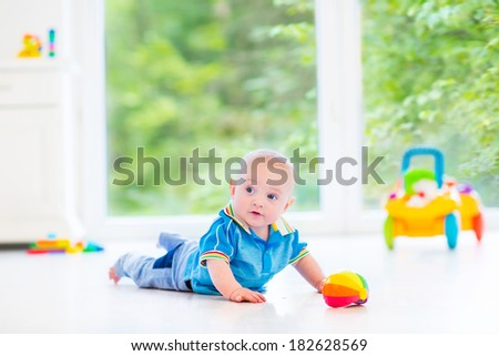 Adorable baby boy playing with a colorful ball and toy car in a sunny nursery with white furniture and white floor and a big garden view window