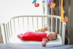 Adorable baby boy sleeping and hugging rabbit doll in cot with mobile toy. Mixed race Asian-German infant lying in sleeper crib attached to parents bed. Child day sleep.