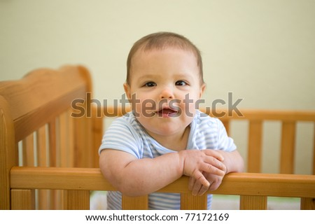 Adorable baby boy smiling standing up in his crib in the nursery
