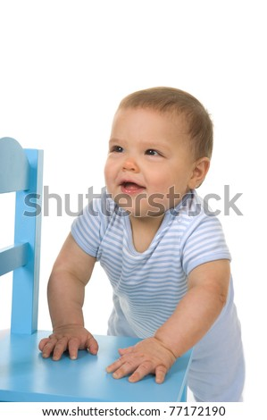 Adorable baby boy smiling standing up in the studio with a blue chair on a white background