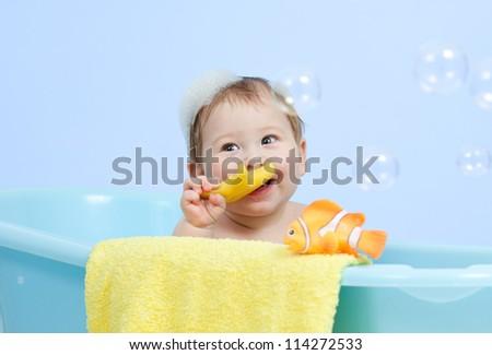 adorable baby boy taking bath in blue tub