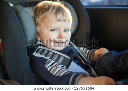 Adorable baby boy with blue eyes in safety car seat