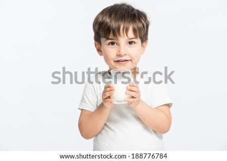 Adorable baby boy with dringking milk with milk mustache holding glass of milk #188776784