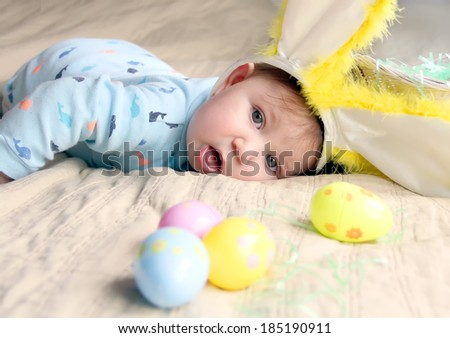 Adorable baby boy with Easter bunny ears and eggs