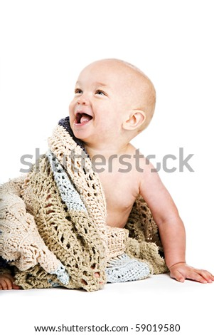 Adorable baby boy wrapped in an afghan.