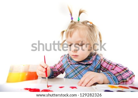 Adorable baby draw with color paints on paper sheet sitting