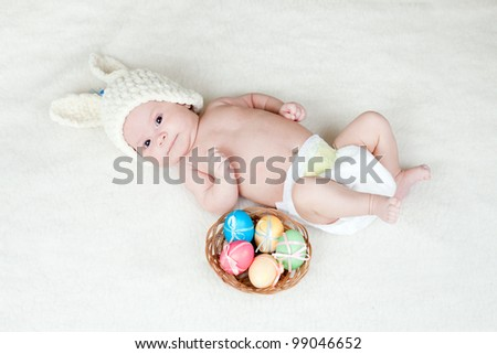 adorable baby dressed in Easter bunny cap with eggs in basket