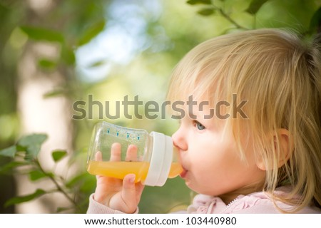 Adorable baby drinking juice with bottle stay under trees in park