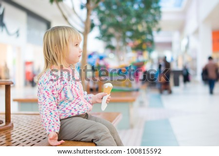 Adorable baby eat ice cream sitting on bench in mall
