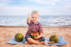 adorable baby eating watermelon on the beach