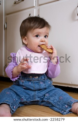 Adorable baby enjoying a cookie on the kitchen floor.